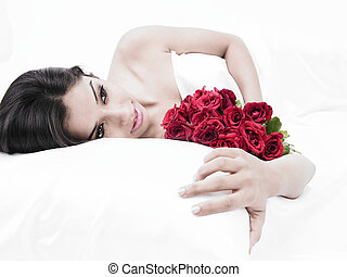 lady in bed with bouquet of roses