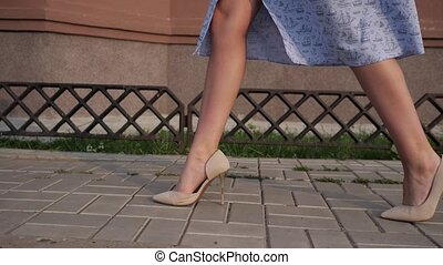 lady in blue dress gorgeous legs in beige high heels walk along street tiled sidewalk on warm day close low angle shot