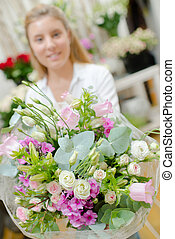 Lady in florists, behind bouquet of flowers
