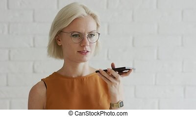 Lady in glasses recording audio message - Attractive young...