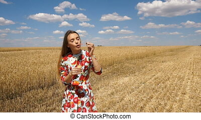 lady in gown stands near a wheat field on a sunny day and inflates soap-bubbles in slow motion