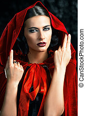 Beautiful brunette woman in black old-fashioned dress and red cloak in the thicket of the magic forest. Gothic style. Fashion.