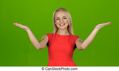 Lady in red on green screen background shows her hands palms up