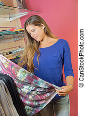 Lady in shop holding item of clothing