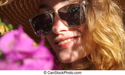 lady in straw hat and sunglasses smiling on camera -...