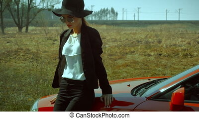 lady in sunglasses and hat with wide brim stands with a red car