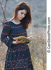 Lady in the field with a book