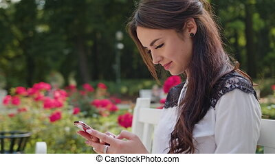 Lady in the Park Using a Phone