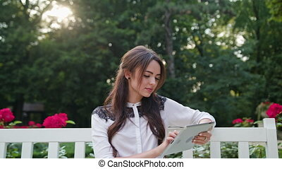 Lady in the Park Using a Tablet