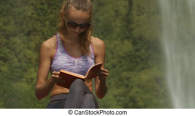 Lady in Violet Top Reads Diary Book on Large Rock - pretty...