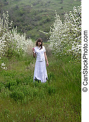 lady in white between blossoming trees