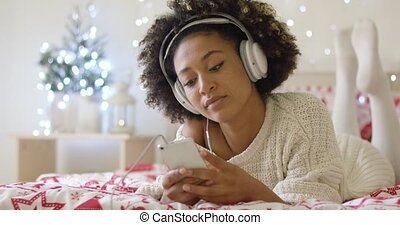 Lady in white sweater on bed listening to music - Attractive...