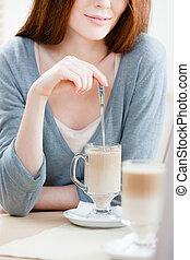 Lady is stirring the milk shake