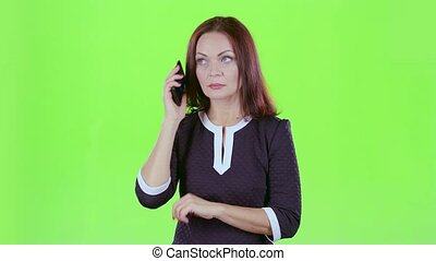 Lady is talking on the phone with her daughters. Green screen
