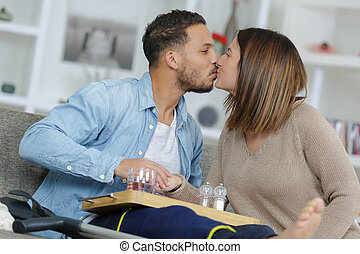 Lady kissing man with leg in splint