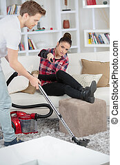 Lady leaning past man vacuuming to change tv channel