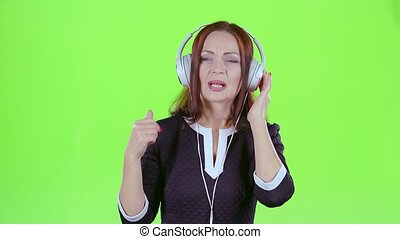 Lady listening to music on headphones. Green screen - Lady...