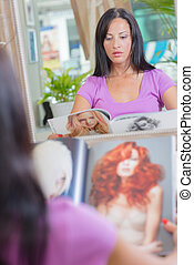 Lady looking at a magazine, reflection in mirror