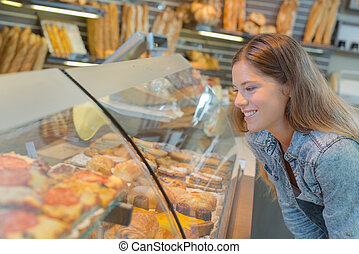 Lady looking at cakes in a bakery