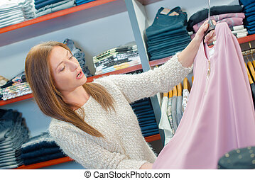 lady looking at pink top in clothes shop