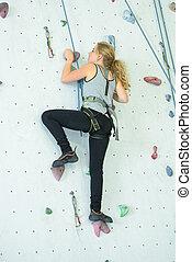 Lady on indoor climbing wall
