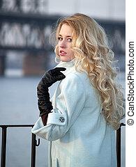 Lady on promenade - Beautiful blonde lady in overcoat on...