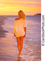 Lady on sandy tropical beach at sunset.