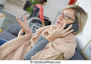 Lady on telephone, woman in wheelchair in background