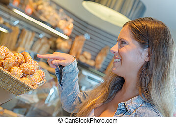 Lady pointing to little cakes in a bakery
