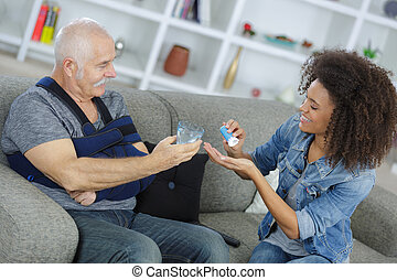 Lady preparing medication for senior man with his arm in a...