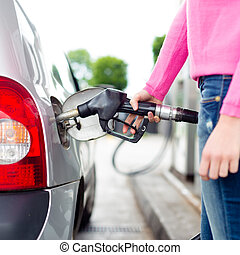 Lady pumping gasoline fuel in car at gas station. - Closeup...