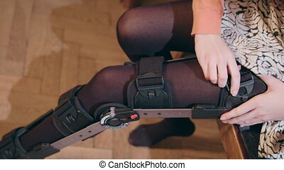 Detail of the lower half of a lady putting on a supportive leg brace. Close-up shot from above
