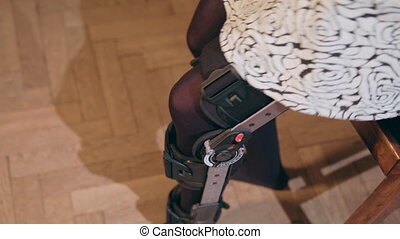 Detail of the lower half of a lady removing a supportive leg brace. Close-up shot