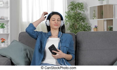 Lady resting listening to music from a smart phone sitting...