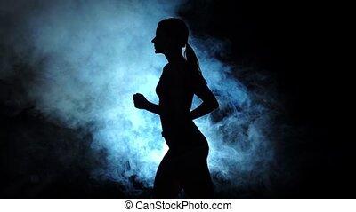 Lady running on a smoky spotlight on black background....