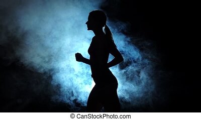 Lady running on a smoky spotlight on black background....