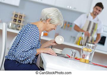 Lady sat at table opening ramekin lid