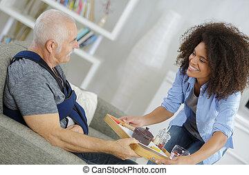 Lady serving meal to injured senior citizen