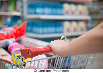 lady shopping with a full filled cart in a supermarket