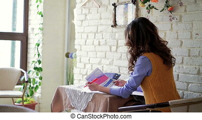Lady sitting at a table in the cafe and viewing documents. The view behind.