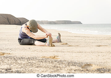 Lady Sitting on a Beach Doing Leg Stretches