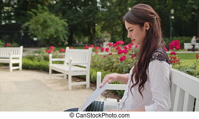 Lady Sitting on Bench in the Park and Using Laptop -...