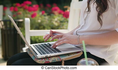 Lady Sitting on Bench in the Park and Using Laptop