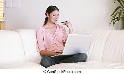Lady sitting on the couch while using her credit card