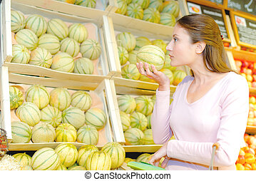Lady smelling a melon for ripeness