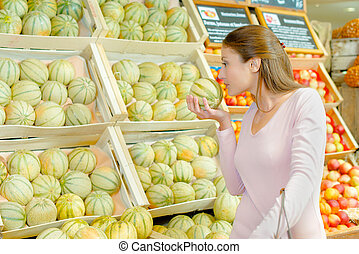 Lady smelling melon in grocers