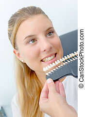 Lady smiling, dentist holding false teeth to match color