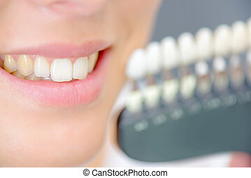 Lady smiling next to teeth samples