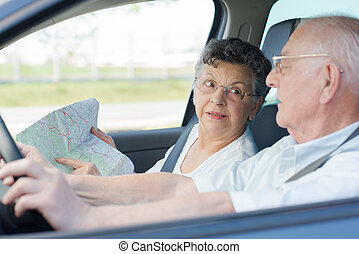 Lady smiling while showing husband directions on map