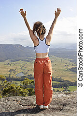 Lady standing on the mountain top with arms stretched out